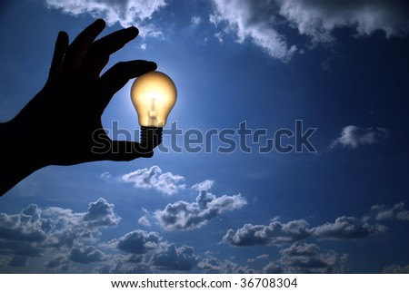 light bulb in the hand on sky background - stock photo