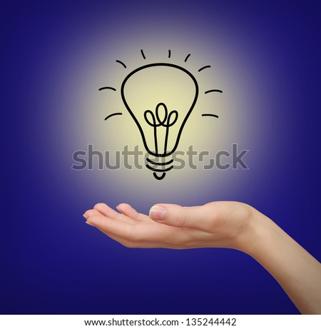 Light bulb in woman hand on blue background - stock photo