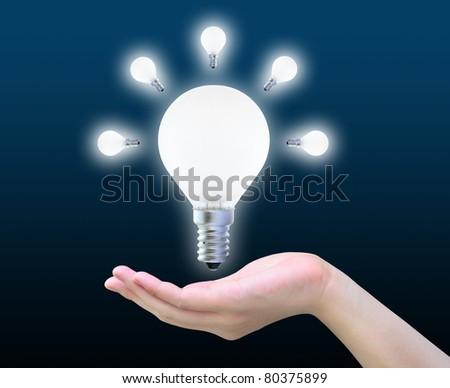 light bulb in women hand on dark - stock photo