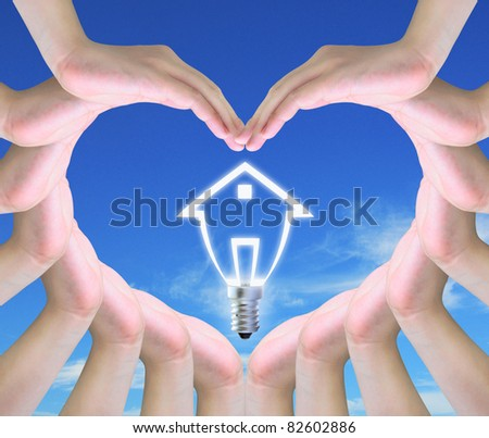 light bulb model of a house in women hands making a symbol of love - stock photo