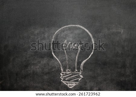Light bulb on a black chalkboard with chalk dust - stock photo