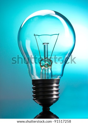 Light bulb on blue background - stock photo