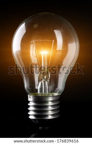 Light bulb on dark background - stock photo