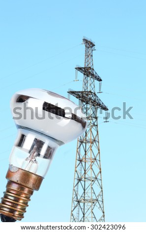 Light bulb on high voltage line background - stock photo