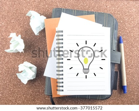 light bulb on notebook with paper trash pen and organizer background idea business concept - stock photo