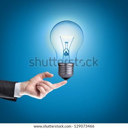 Light bulb on tip of finger on businessman.Blue background. - stock photo