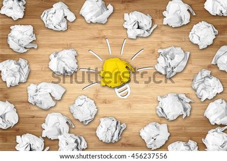 light bulb symbol on desk with many paper balls - stock photo