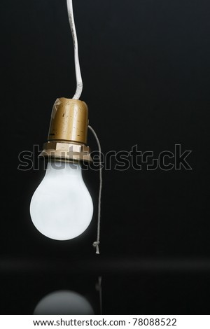 Light Bulb turned off, isolated on black background and reflecting on mirror. - stock photo