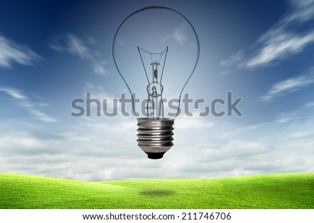 Light bulb with blue sky in field. Environment, eco technology and solar energy concept.