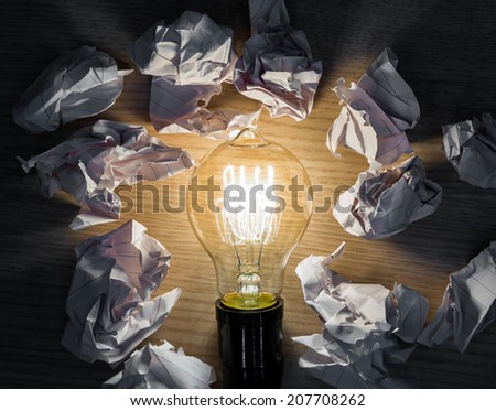 Light bulb with Crumpled paper on wood background - stock photo