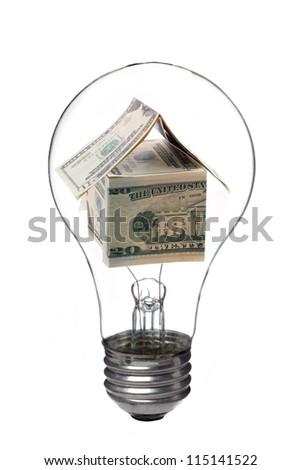 Light bulb with house made of dollar inside - stock photo