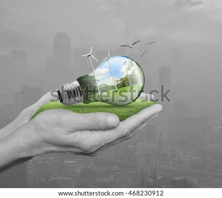 Light bulb with wind turbines, birds and forest inside in hands over pollution city, Ecological concept