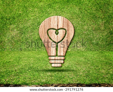 Light Bulb wood icon and heart shape inside in grass room,Eco concept. - stock photo