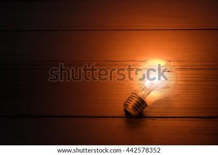 Light bulbs glow on a wooden table.  idea concept - stock photo