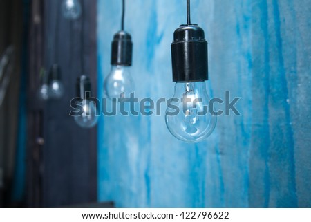 Light bulbs hanging on an electric wire on a blue background - stock photo