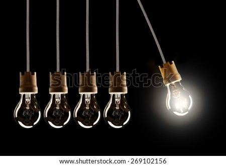 Light bulbs in row with single one in motion and shinning, isolated on black background - stock photo