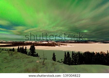 Light clouds and Northern Lights or Aurora borealis or polar lights on night sky over snowy winter landscape of Lake Laberge  Yukon Territory  Canada - stock photo