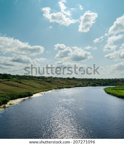 light clouds in blue sky over river with reflections - stock photo