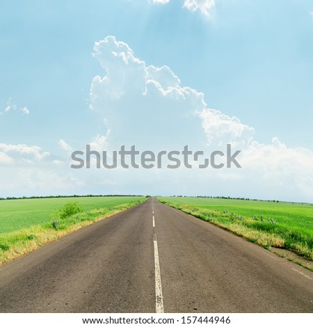 light clouds over asphalt road to horizon - stock photo