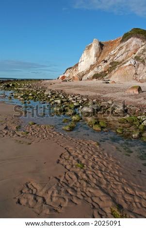 Light-colored cliffs on a sandy, rocky beach at dusk. - stock photo