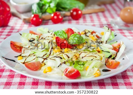 Light diet vegetable salad with Chinese cabbage, sweet corn, cherry tomatoes dressed with balsamic vinegar and olive oil on the  white plate on kitchen tablecloth with different bright ingredients - stock photo