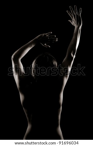 Light emphasizing the Artistic Muscles of a Woman's Back and Arms - stock photo
