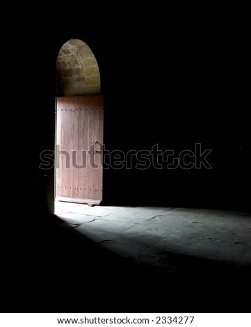 Light entering a dark room through a door in an ancient cathedral. - stock photo