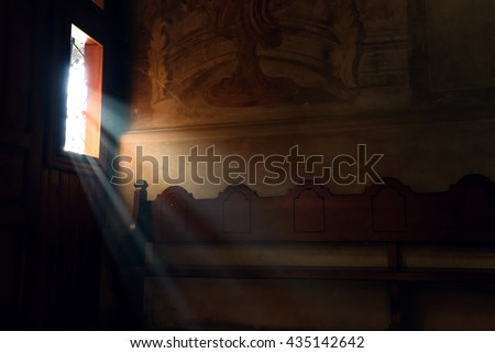light falling through window in old church on wooden bench, peaceful moment - stock photo