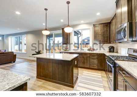 Light Filled Northwest Kitchen Design With Kitchen Island, Natural Brown  Cabinets Topped With Granite Countertops