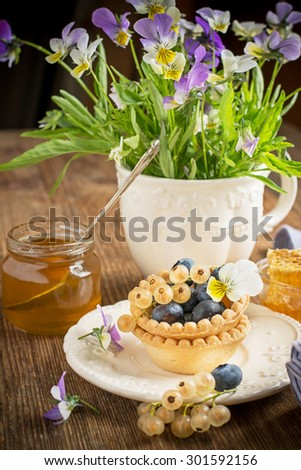Light fresh crunchy pastry tartlet of fresh blueberries and white currants on a la carte dishes with honey comb in the background Bunch of viola on a wooden background. selective Focus - stock photo