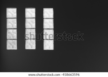 Light from a glass block and dark wall.