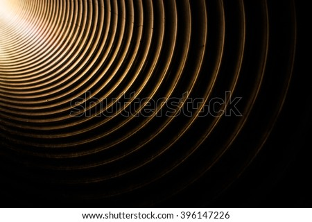 Light getting into the large metal tunnel pipe on a kids playground - stock photo