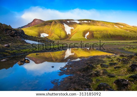 Light golden dawn illuminates the mountains and glaciers national park Landmannalaugar. The  sunrise in Iceland - stock photo