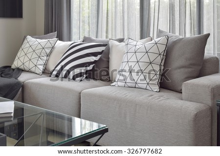 Light gray sofa with varies pattern pillows in modern living corner - stock photo