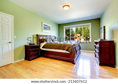 Light green bedroom with hardwood floor and carved wood furniture