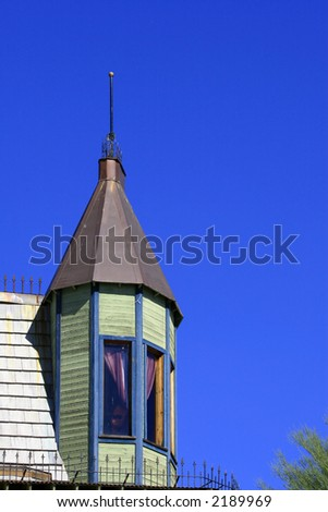 Light green Victorian turret with a lightning rod is presented against a brilliant blue desert sky - stock photo