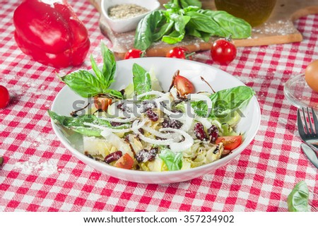 Light italian vegetable salad with Chinese cabbage, kidney bean, cherry tomatoes dressed with balsamic vinegar and olive oil on the  white plate on kitchen tablecloth with different bright ingredients - stock photo
