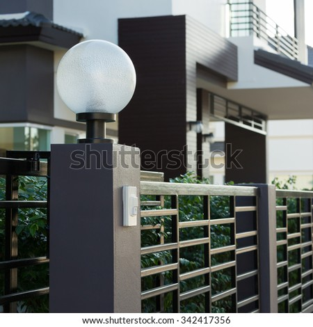 light lamp modern style on front gate of decoration residential house - stock photo