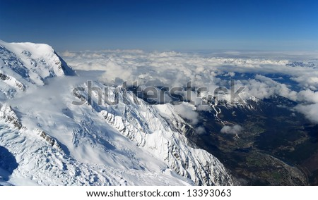 Light layer of white clouds and blue sky over spring valley, snow mountain in the foreground - stock photo