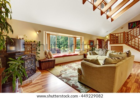 Light living room with hardwood floor and high ceiling with wooden beams. Has comfortable sofa set. View of staircase. - stock photo