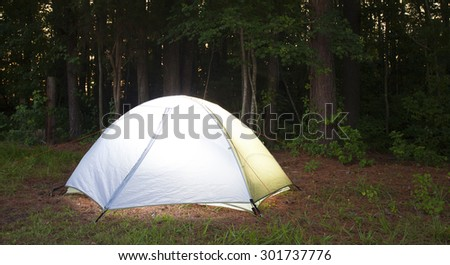 Light nylon tent that is pitched in a thick forest - stock photo