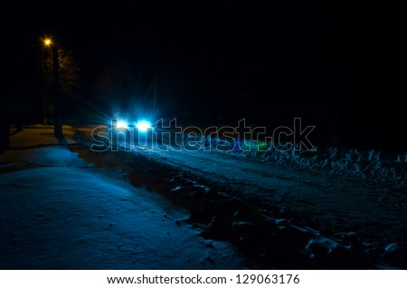 Light of car headlights inundates a nightly snow bound road. - stock photo