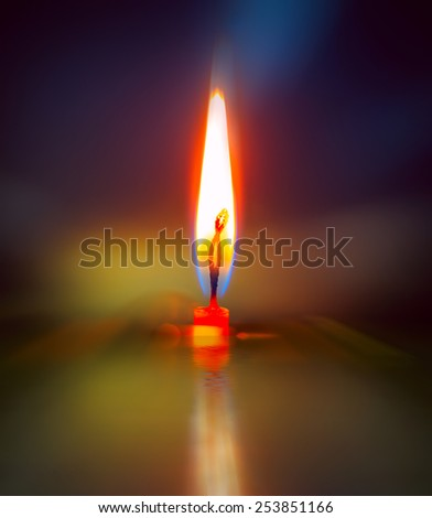 Light of single candle in darkness - stock photo
