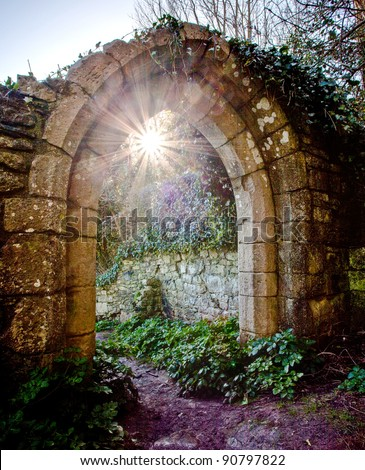 Light of the world - the sun peeps through an old arched doorway at the ruined St Andrew's Church at Church Ope Cove, Portland, Dorset. - stock photo