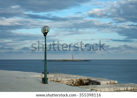 Light on sidewalk in coast town of Porec,on background lighthouse.
