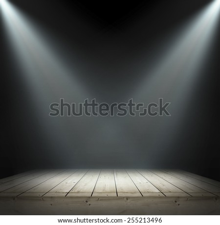 Light on wooden table on black background