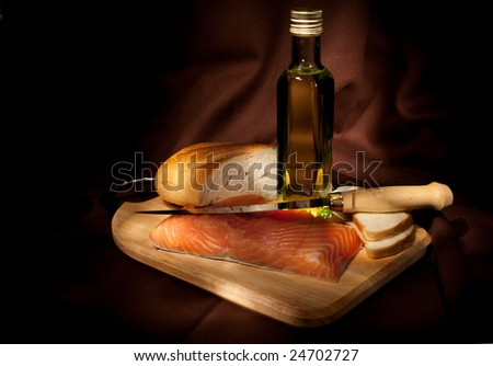 Light painting shot of salmon, olive oil and bread - stock photo