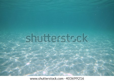 Light patterns on flat bottom covered with white sand in shallow water. - stock photo