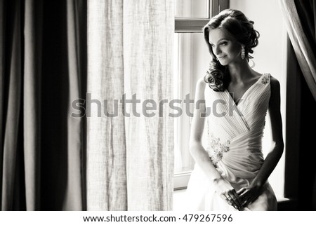 Light photo of the bride next to the window