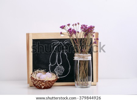 light pink eggs are lying in hay in wicker basket, a glass vase with pink flowers is nex to the basket with eggs, a chalk board with Easter bunny drawn on board, Easter decorations, isolated